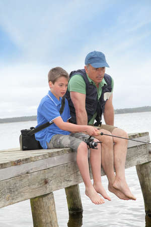 Father and son fishing in lake photo
