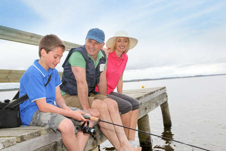 Family sitting on a pontoon with kid fishing photo