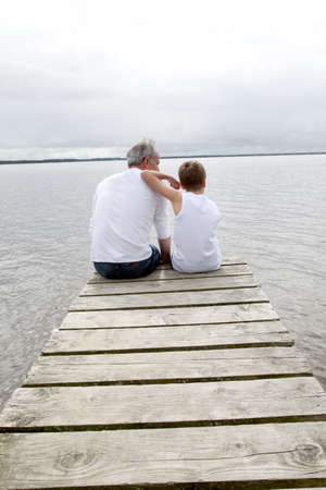Portrait of father and son sitting on a pontoon photo