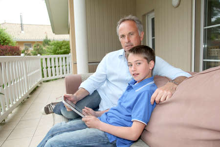 men 45 years: Father and son sitting in sofa with electronic tablet Stock Photo