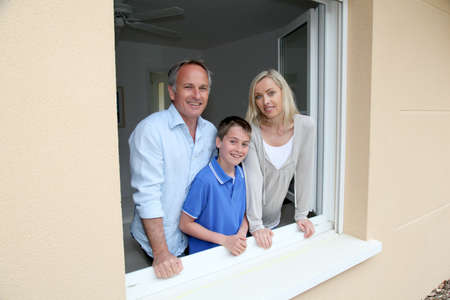 Portrait of family standing by house window photo