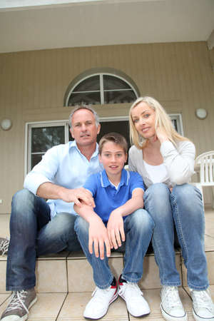 Portrait of family sitting on the front door stairs photo