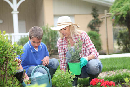 Mother and child planting flowers in house garden photo