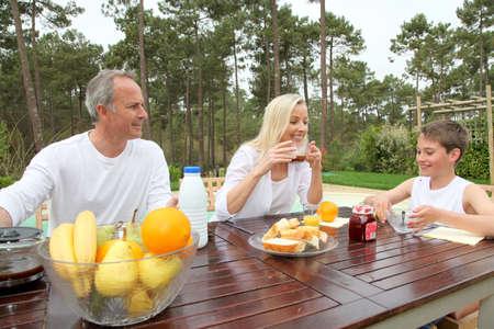 breakfast garden: Family having breakfast in house garden