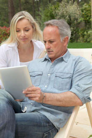 Couple resting in long chairs with electronic tablet photo