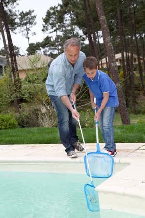 swimmingpool: Father and son cleaning swimming-pool Stock Photo