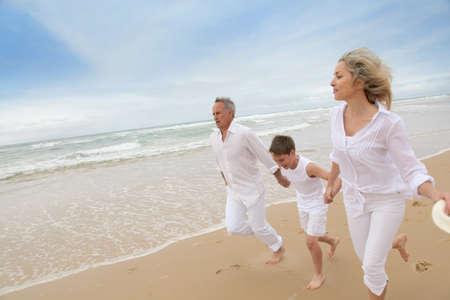Family running on a sandy beach photo