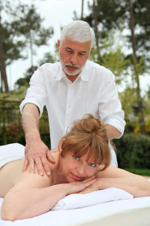 Senior woman having a massage in spa center photo