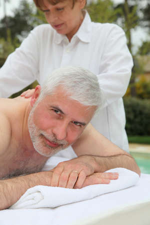 Portrait of senior man laying on a massage bed photo