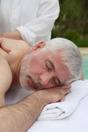 Portrait of senior man laying on a massage bed Stock Photo - 9479105