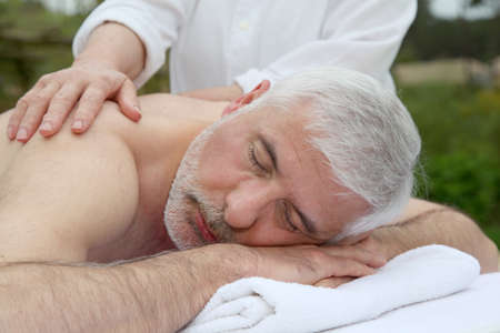 Portrait of senior man laying on a massage bed Stock Photo - 9479111