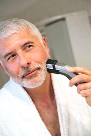 electric razor: Senior man in bathroom with electric razor