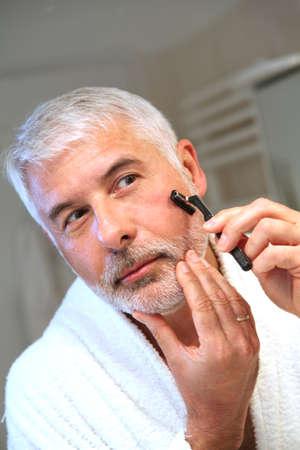 Portrait of senior man shaving beard
