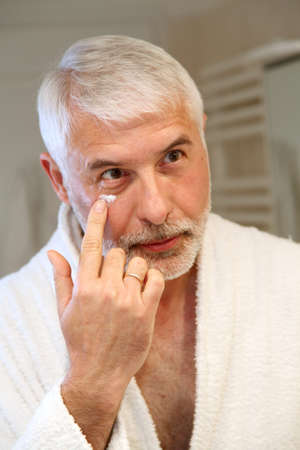 moisturizing: Portrait of senior man applying moisturizing cream