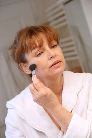 Senior woman putting makeup on Stock Photo - 9479988