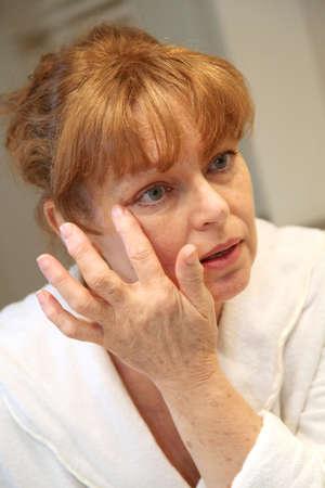 beautycare: Portrait of senior woman applying moisturizing cream
