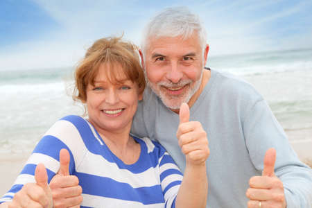 senior couples: Happy senior couple with thumbs up at the beach
