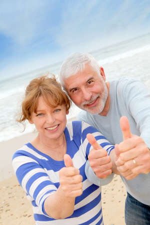 Happy senior couple with thumbs up at the beach photo