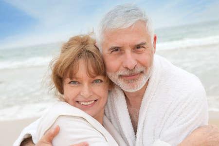 Senior couple at the beach with spa bathrobe photo
