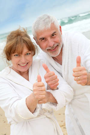 Happy senior couple on spa resort beach photo