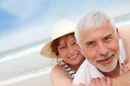 Portrait of happy senior couple on a sandy beach photo