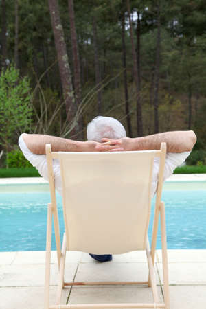 Senior man relaxing in deck chair by a pool Stock Photo - 9479098