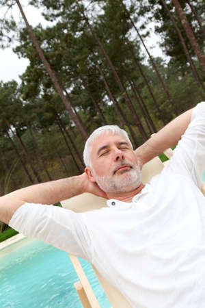 Senior man relaxing in deck chair by a pool photo