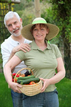 Senior couple standing in kitchen garden photo