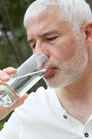 Senior man drinking fresh water photo