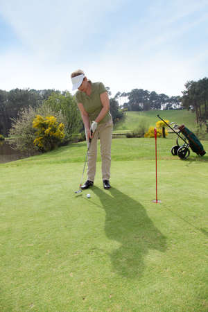 Senior woman playing on golf course photo