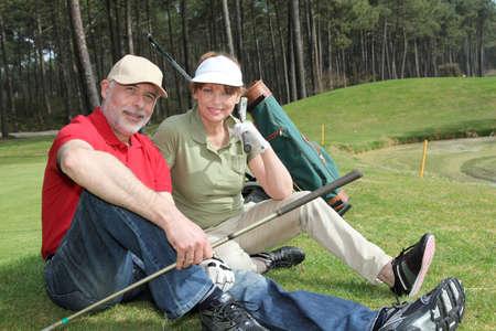 Senior people sitting on golf course photo