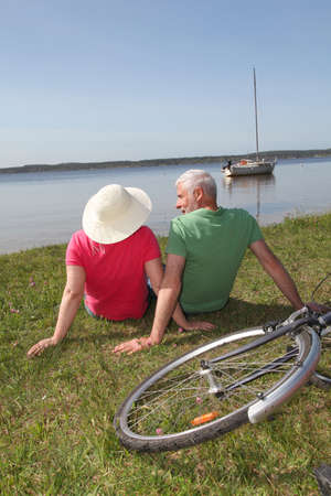 happy old people: Senior couple riding bicycle in summer Stock Photo