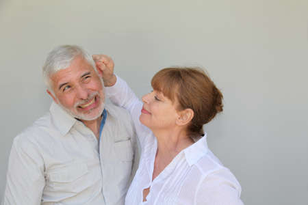 pulling hair: Senior woman pulling on husbands ear Stock Photo