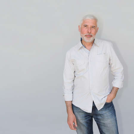 Senior man standing on white background photo