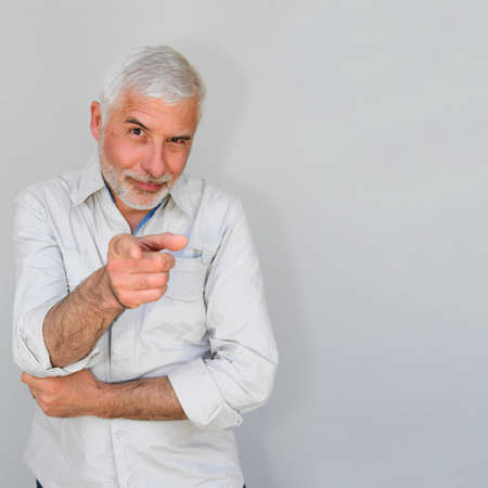 Senior man on white background pointing at camera photo