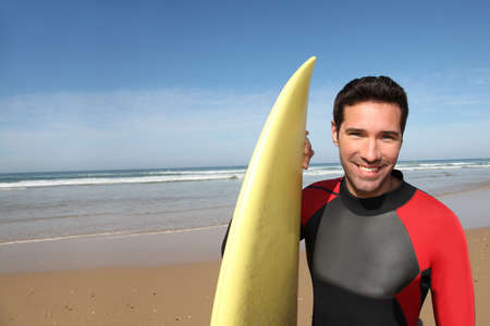 Portrait of young man with surfboard photo