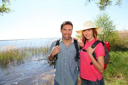 rambling: Happy couple hiking by a lake Stock Photo