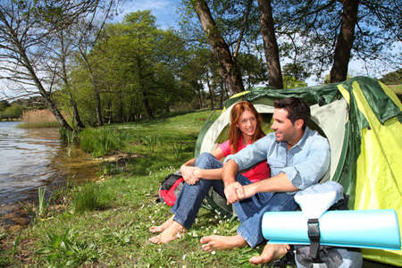 Happy couple sitting by camp tent photo