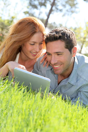 Portrat of couple laying down the grass with touchpad photo