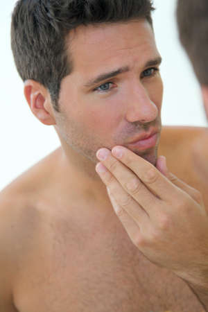 beautycare: Portrait of attractive man looking at mirror