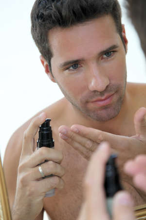 moisturize: Handsome man applying moisturizer in front of mirror Stock Photo