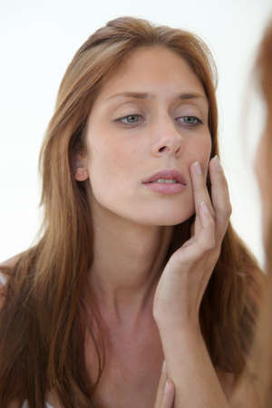 beautycare: Beautiful woman looking in a mirror