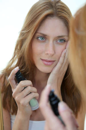 beautycare: Beautiful woman putting foundation on her face