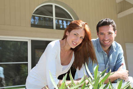Young couple sitting in front of their new house photo