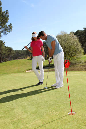 Couple playing golf on a sunny day photo