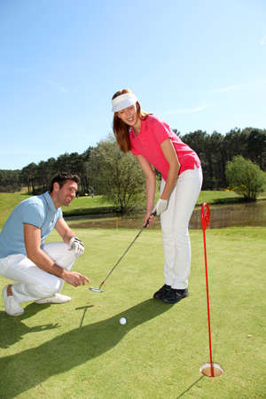 teaching adult: Woman learning how to play golf