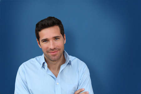 Retrato de hombre guapo permanente sobre fondo azul