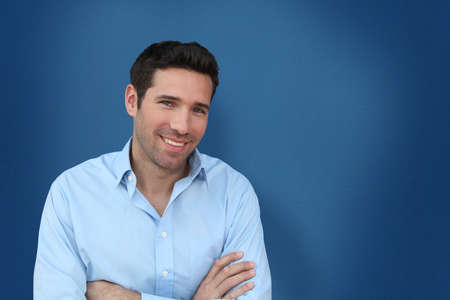Portrait of handsome man standing on blue background photo