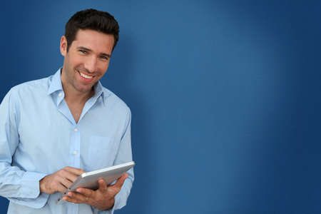 touchpad: Attractive man with touchpad on blue background