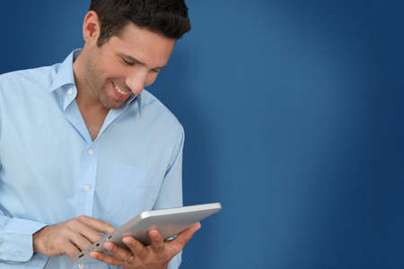 Attractive man with touchpad on blue background photo